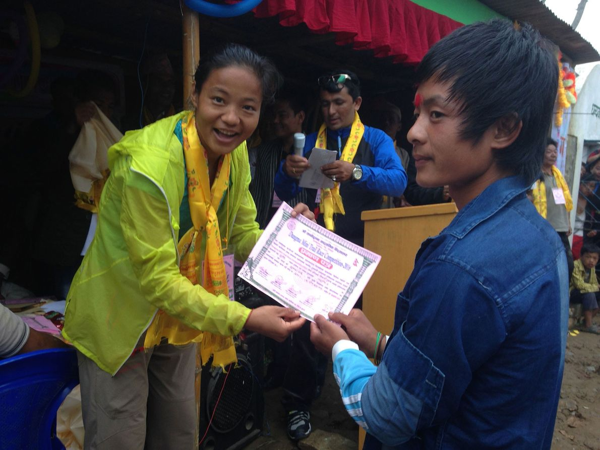 Imagem da atleta Mira Rai a entregar os certificados aos vencedores da corrida na sua aldeia.