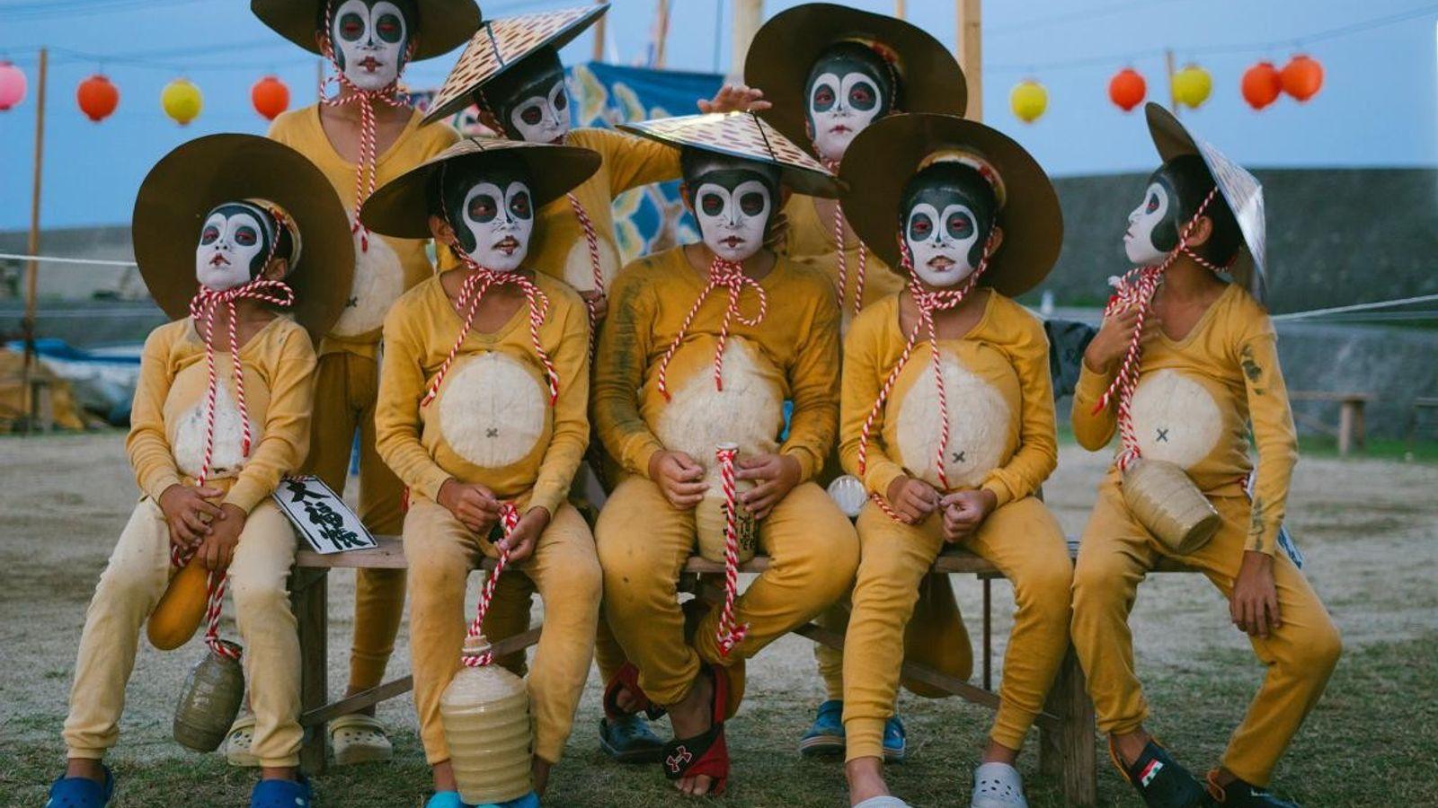 Um grupo de crianças vestidas de tanuki