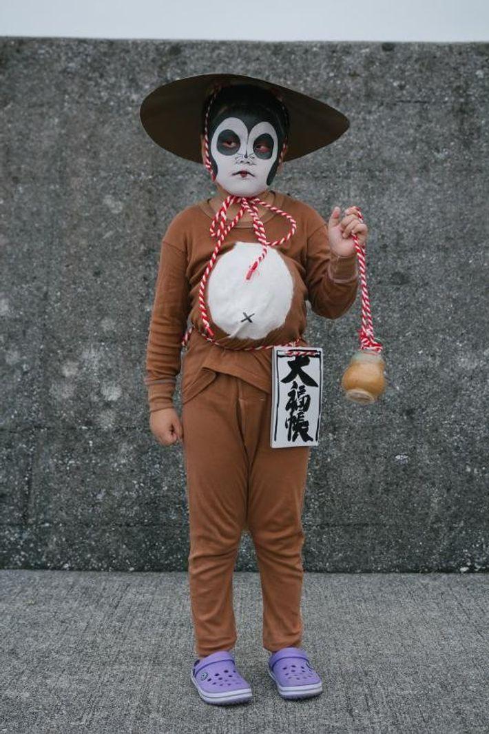 Uma criança, vestida de uma personagem popular do folclore japonês