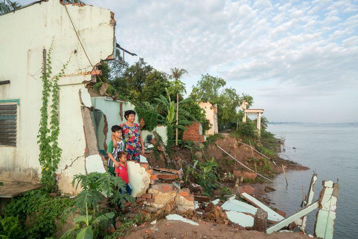 Ha Thi Be e os seus dois netos fotografados nas ruínas da sua casa ancestral na ...