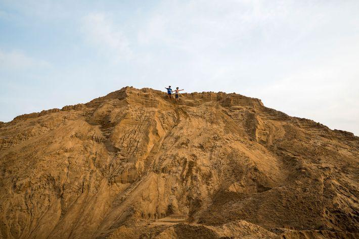 Nguyen Gia Lac, de 10 anos, e Nguyen Trung Kien, de 12, brincam num monte gigante ...