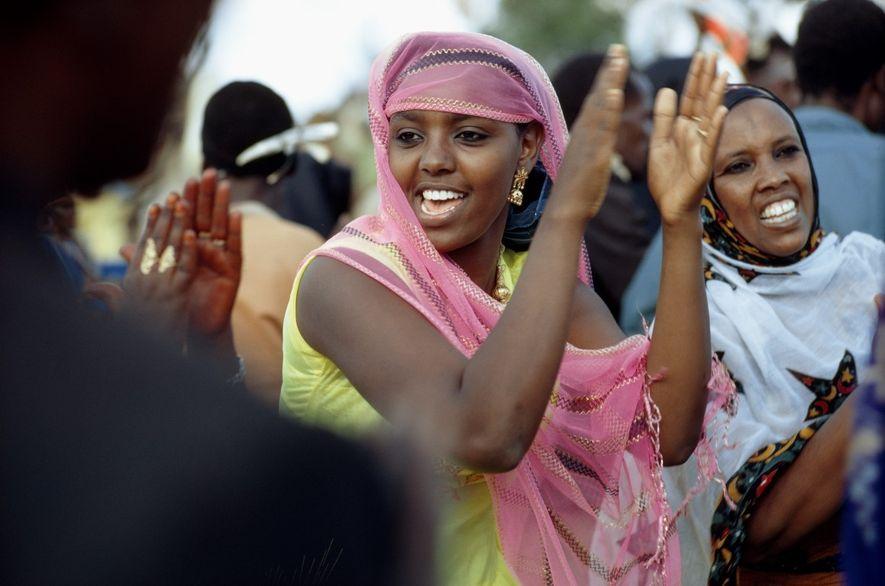 Mulheres somalis cantam e aplaudem numa dedicação hospitalar.