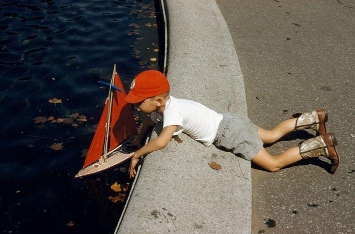 Uma criança com botas de cowboy lança um barco no lago de um parque.