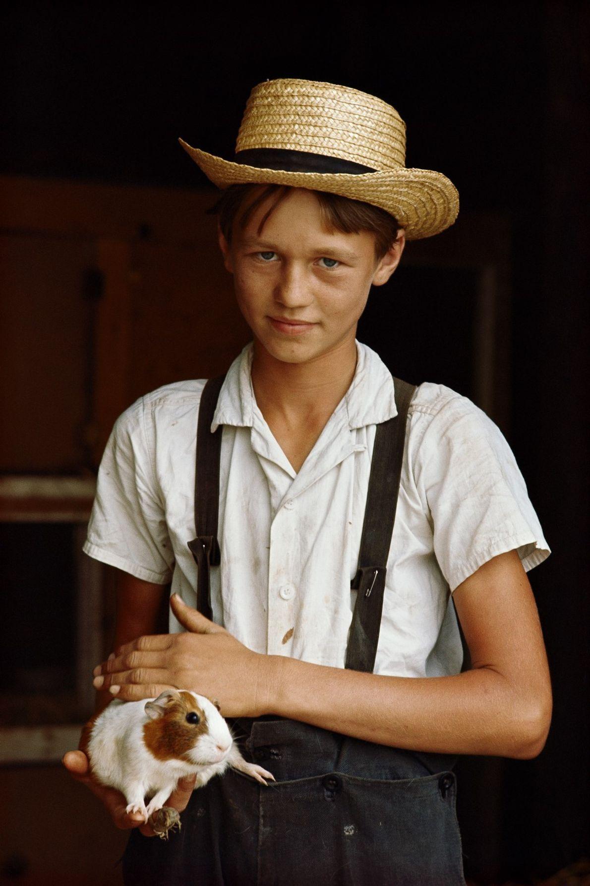 Um rapaz de uma comunidade Amish, com um chapéu de palha e suspensórios, com um ...