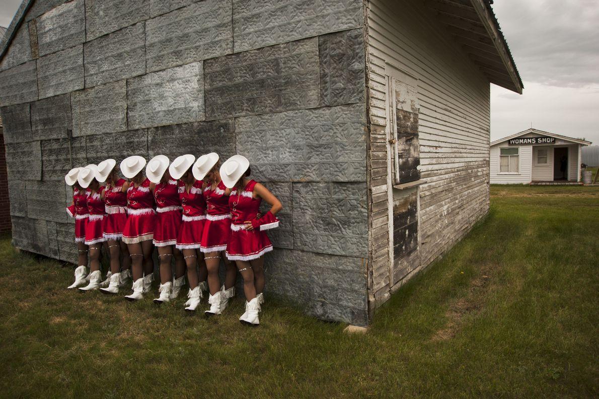 Bailarinas posam para fotografias publicitárias numa aldeia pioneira.