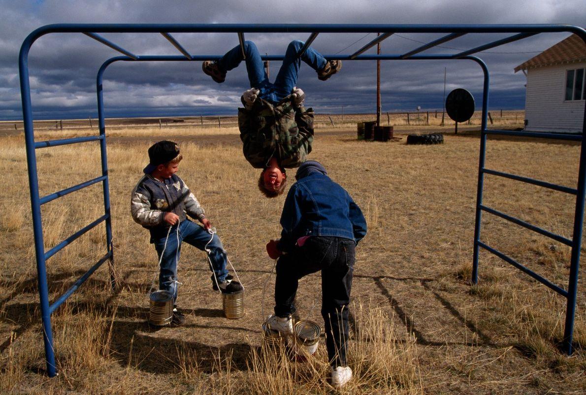 Três crianças brincam em Lone Tree Bench