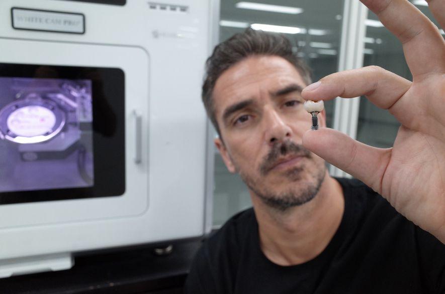 Fotografia do Dr. Miguel Stanley com dente criado através da tecnologia de impressão 3D.