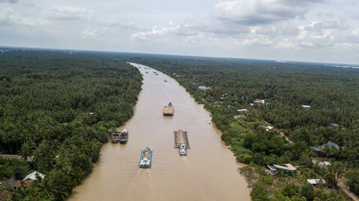 Balsas com areia descem o canal de Cho Gao em direção à cidade de Ho Chi ...