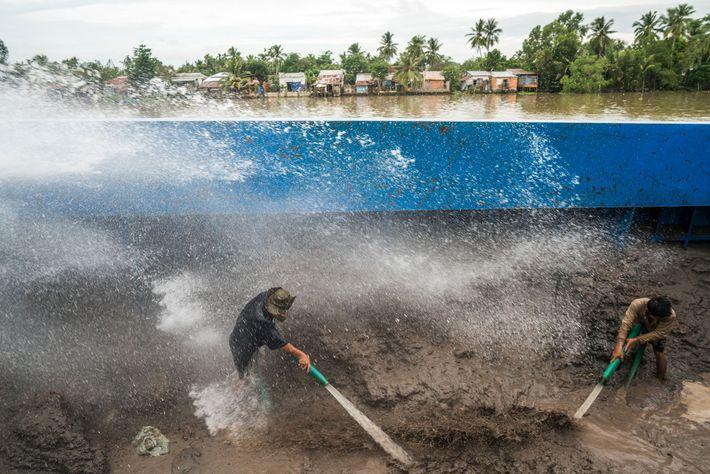 Trabalhadores de uma balsa de transporte de areia perto da cidade de Can Tho limpam com ...