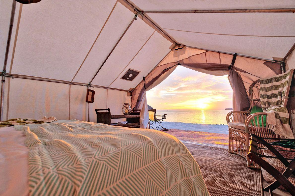O sol brilha sobre o oceano do lado de fora da tenda luxuosa no resort Todos …