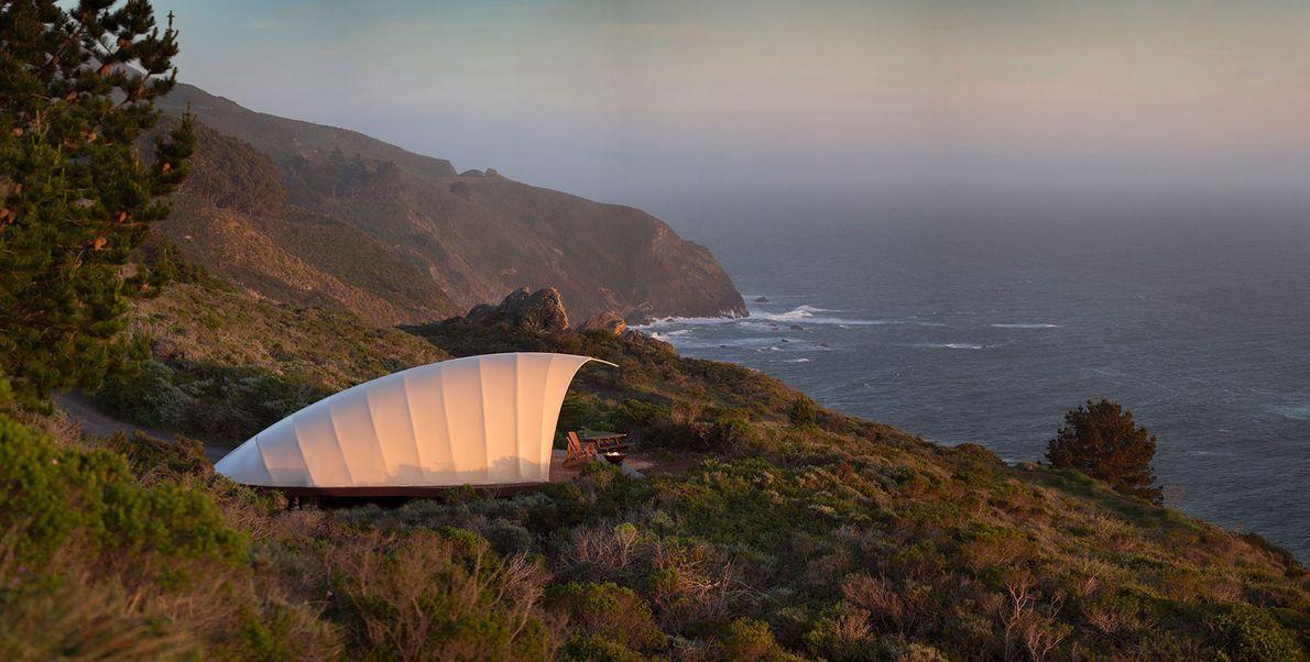 O alpendre privado das tendas do resort de luxo Treebones tem vista para a costa rochosa …