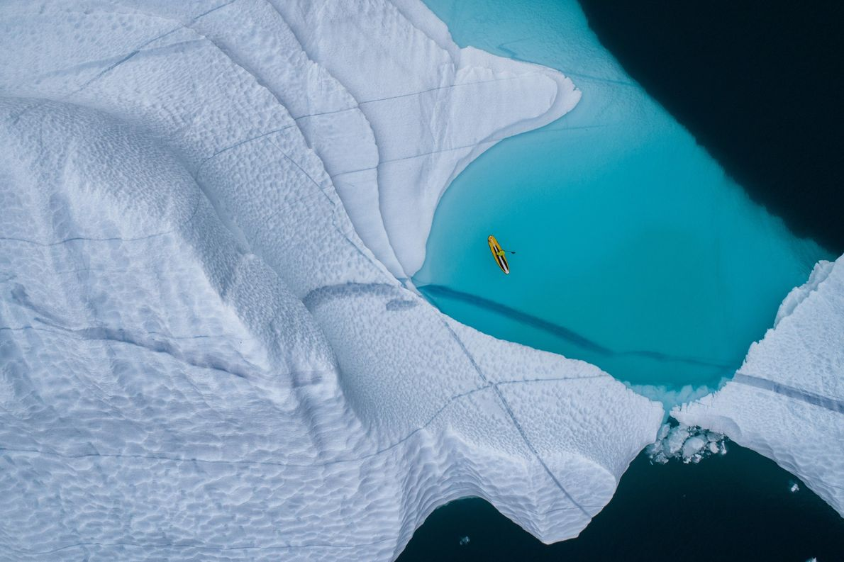 Um paddleboarder a deslizar pelas águas frígidas do Mar da Gronelândia.