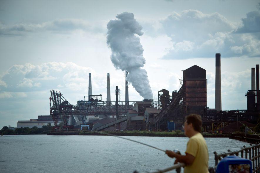 Um homem a pescar junto a uma fábrica de carvão, em Detroit.