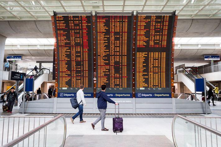 Passageiros verificam o painel de partidas, no aeroporto Charles de Gaulle, em Paris, França.