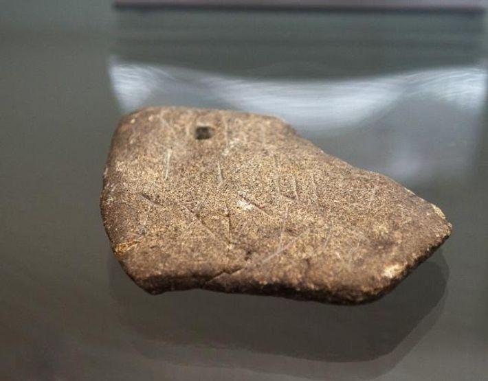 Uma das pedras com inscrições, pertencente ao conjunto de artefactos encontrados no Alvão, exposta no Museu ...