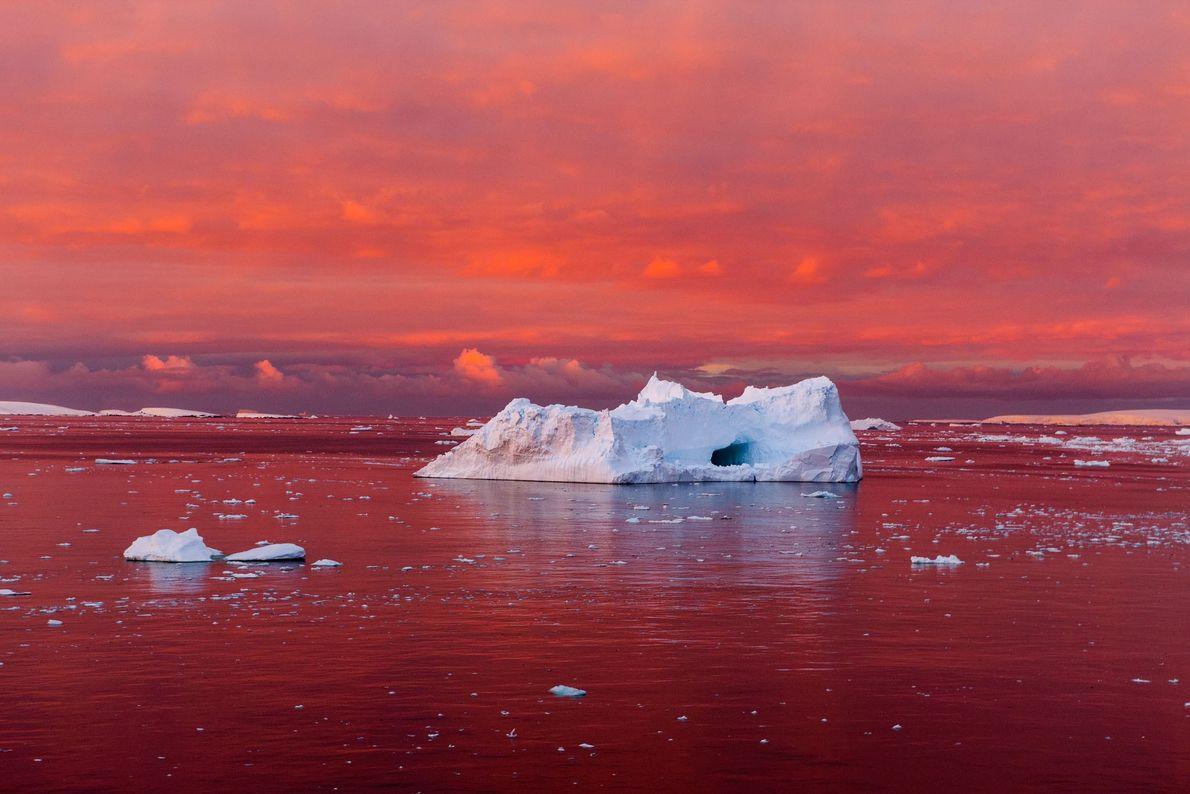 Um pôr do sol surpreendente pinta o Canal Lemaire em tons de vermelho, na costa oeste ...