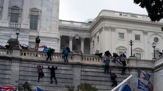 Uma multidão de apoiantes violentos do presidente Donald Trump escala um dos muros do Capitólio dos ...