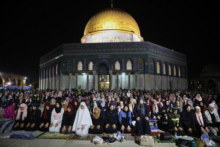 Cúpula de Pedra iluminada atrás dos muçulmanos