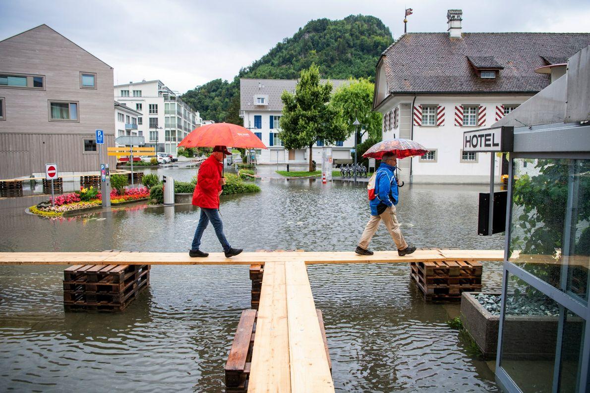 Na Suíça, pessoas caminham sobre passadiços de madeira na praça de uma vila inundada.