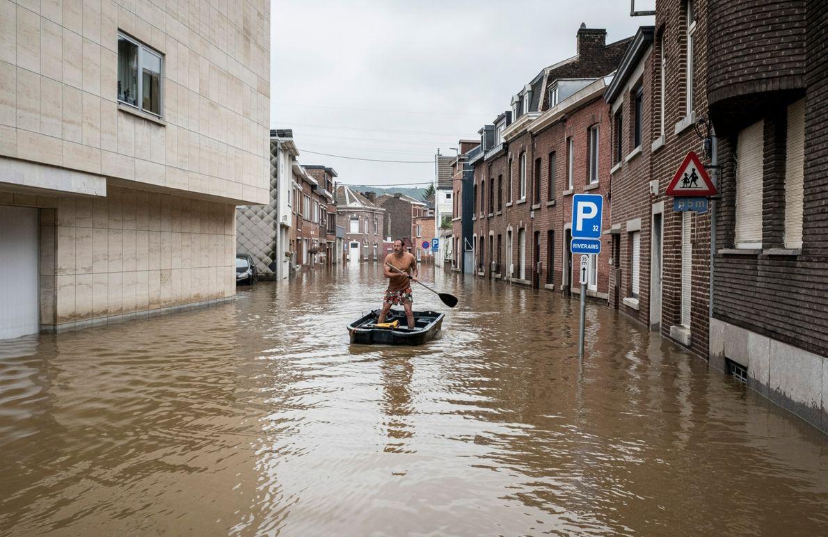 Um homem rema um barco ao longo de uma rua residencial inundada na Bélgica, na sexta-feira, ...
