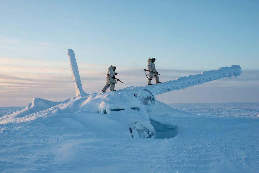 Soldados canadianos sobem aos destroços de um avião, a cerca de 1600 km a sul do ...