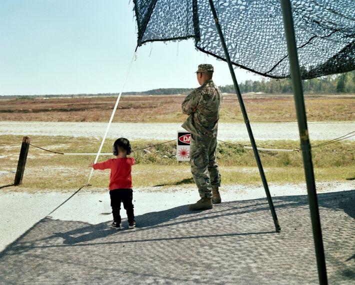 John e o filho, Teo, observam tanques a disparar