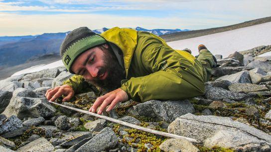 Um investigador examina a haste de madeira de uma flecha que emergiu na mancha de gelo ...