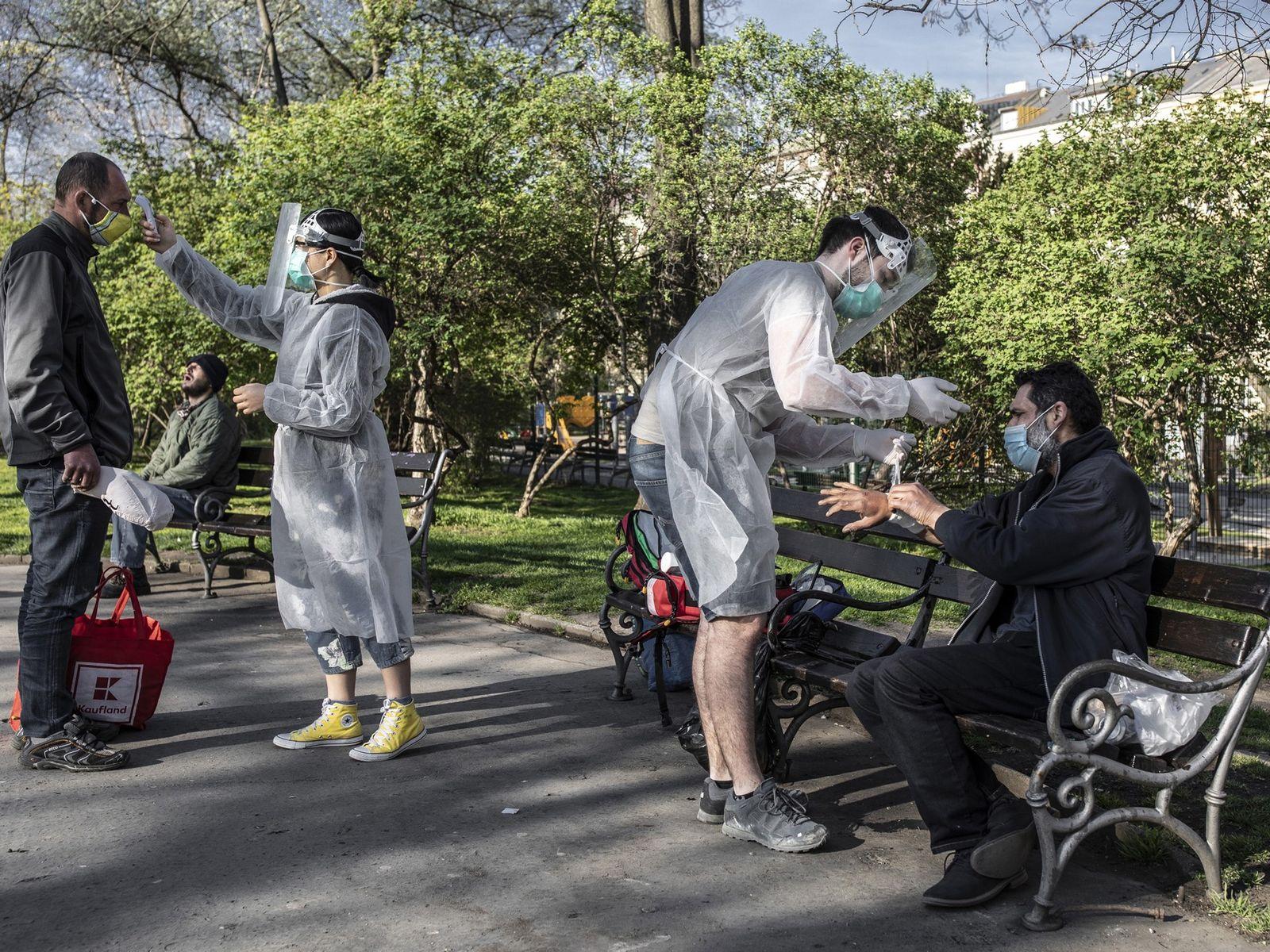 Estudantes de medicina cuidam de pessoas sem-abrigo num parque em Praga, durante a pandemia de COVID-19.
