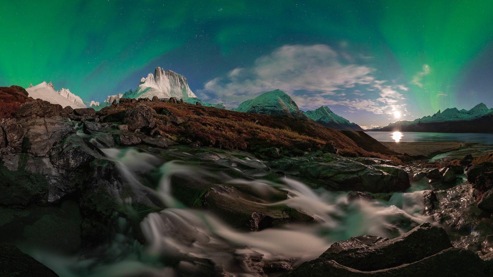 Uma aurora a brilhar contra o céu noturno, perto do fiorde Tasermiut. O fiorde tem montanhas ...