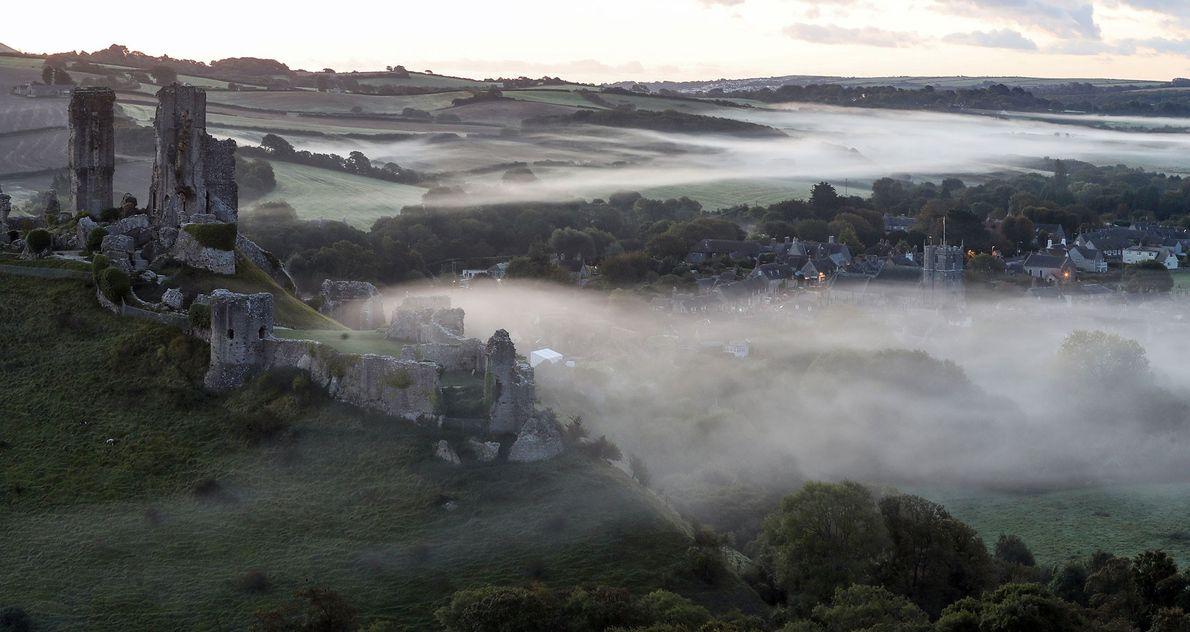 Uma bruma rasteira envolve a aldeia de Corfe Castle em Dorset