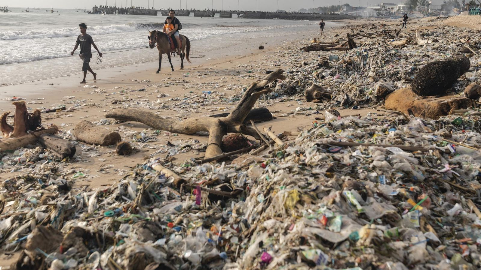 Turistas a passear a cavalo na praia de Kedonganan, em Bali, no dia 27 de janeiro ...