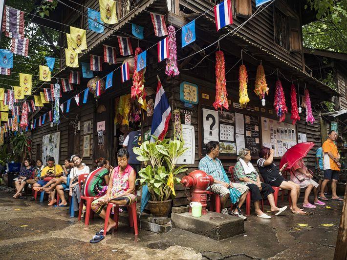 Os habitantes de Pom Mahakan Fort abrigam-se das chuvas da monção.