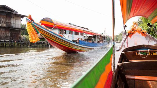 Embarcações coloridas navegam ao longo do rio Chao Phraya, em Bangkok.