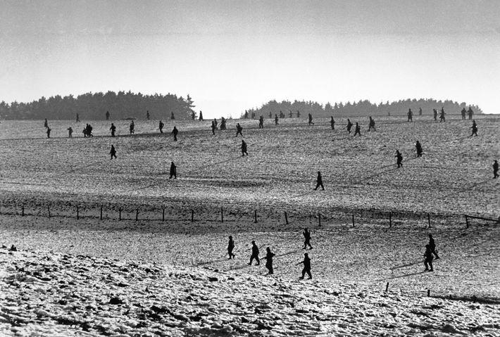 Ainda a recuperar do ataque de 16 de dezembro, soldados dos EUA avançam por um campo ...