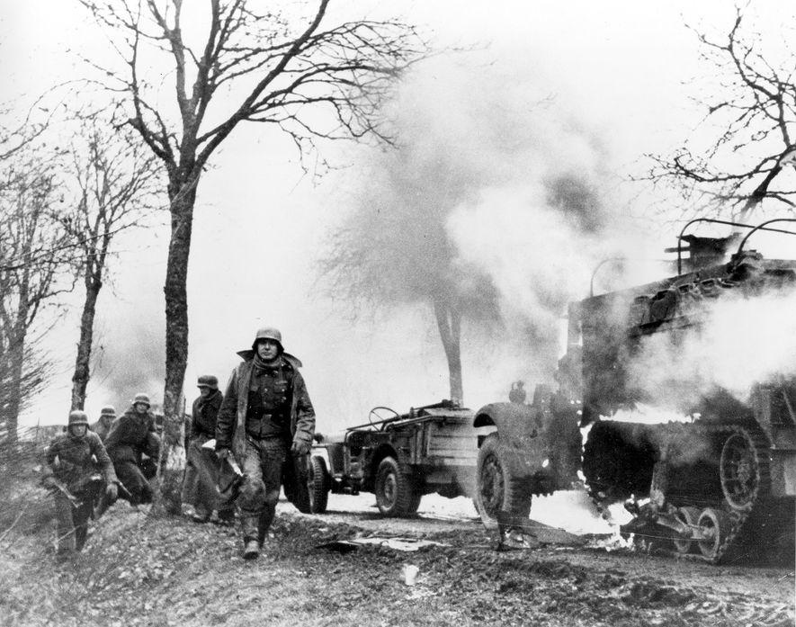 Soldados de infantaria alemães a passar por veículos americanos em chamas durante a Batalha das Ardenas. ...