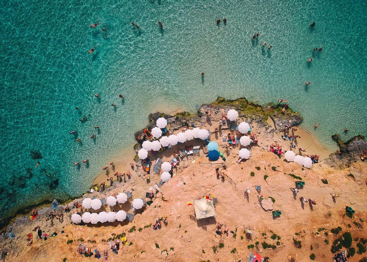Veraneantes mergulham numa lagoa azul, entre as ilhas de Malta, Comino e Cominotto. Anteriormente um refúgio ...