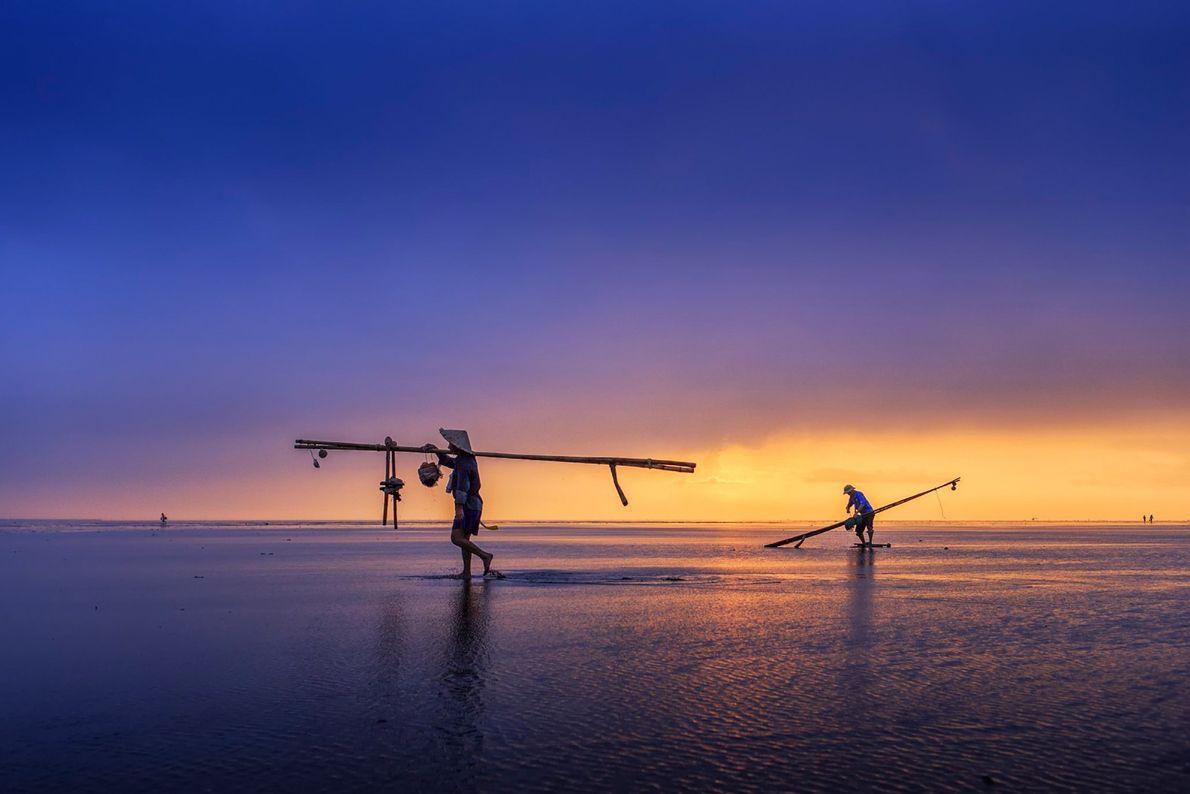 Pescadores retiram postes e redes para evitar uma tempestade em Thai Binh, no Vietname. Esta província ...