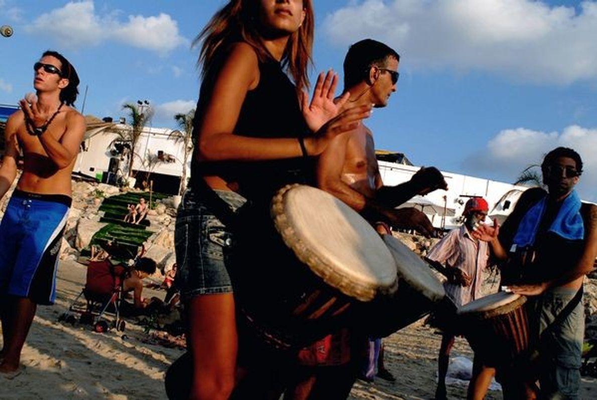 Fotografia: uma mulher e um homem tocam tambores na praia