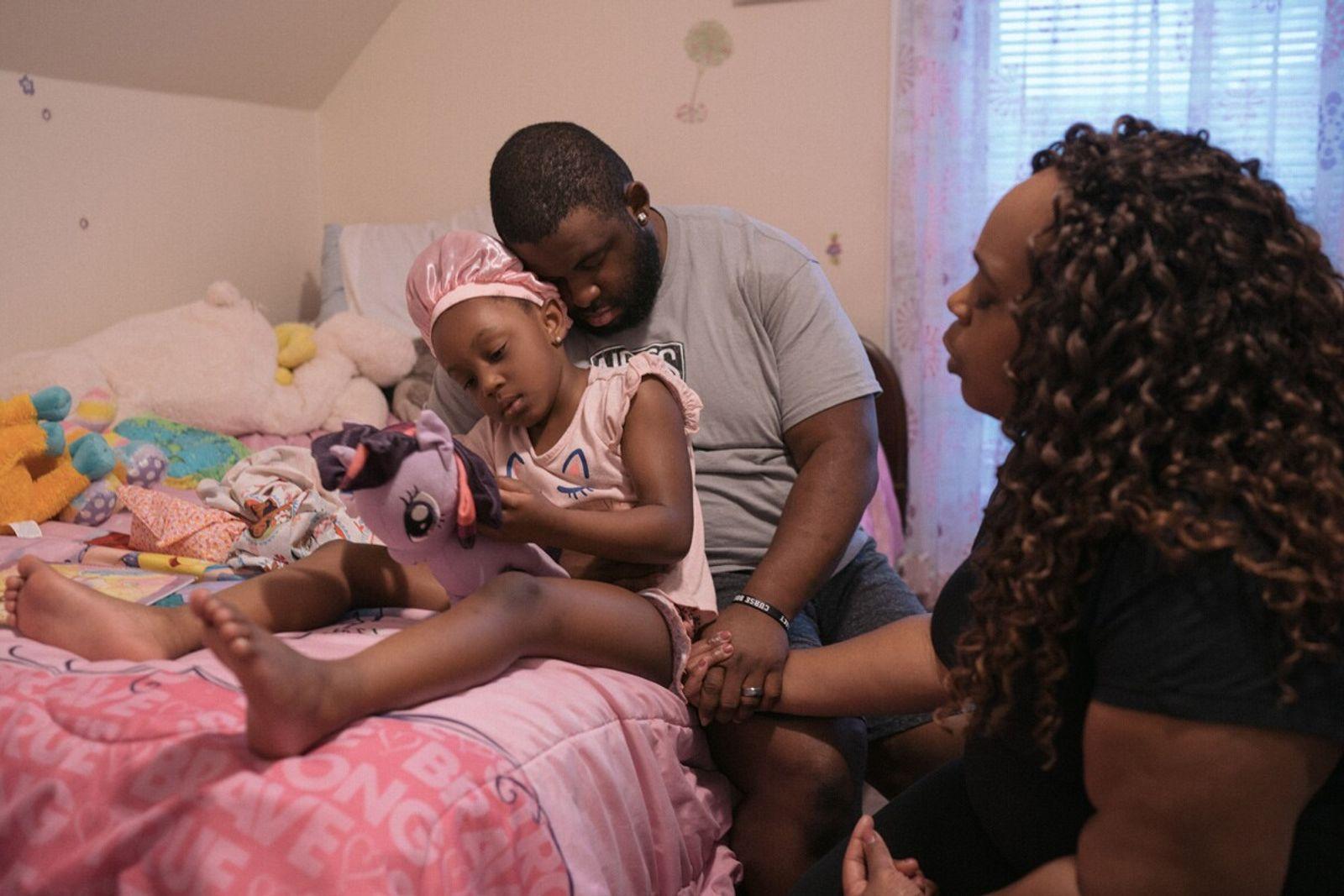 Anthony Hallett e Jessica Blass-Hallett fazem uma oração com a sua filha, Ava, na sua casa ...