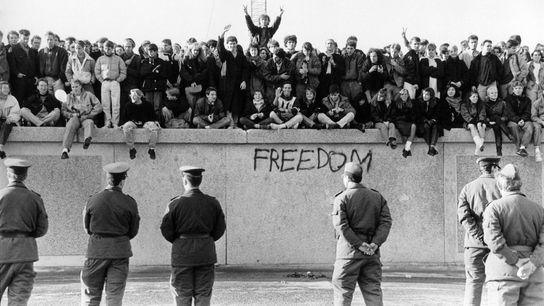 Alemães ocidentais escalam o Muro de Berlim perante os guardas da Alemanha de leste, quando o ...