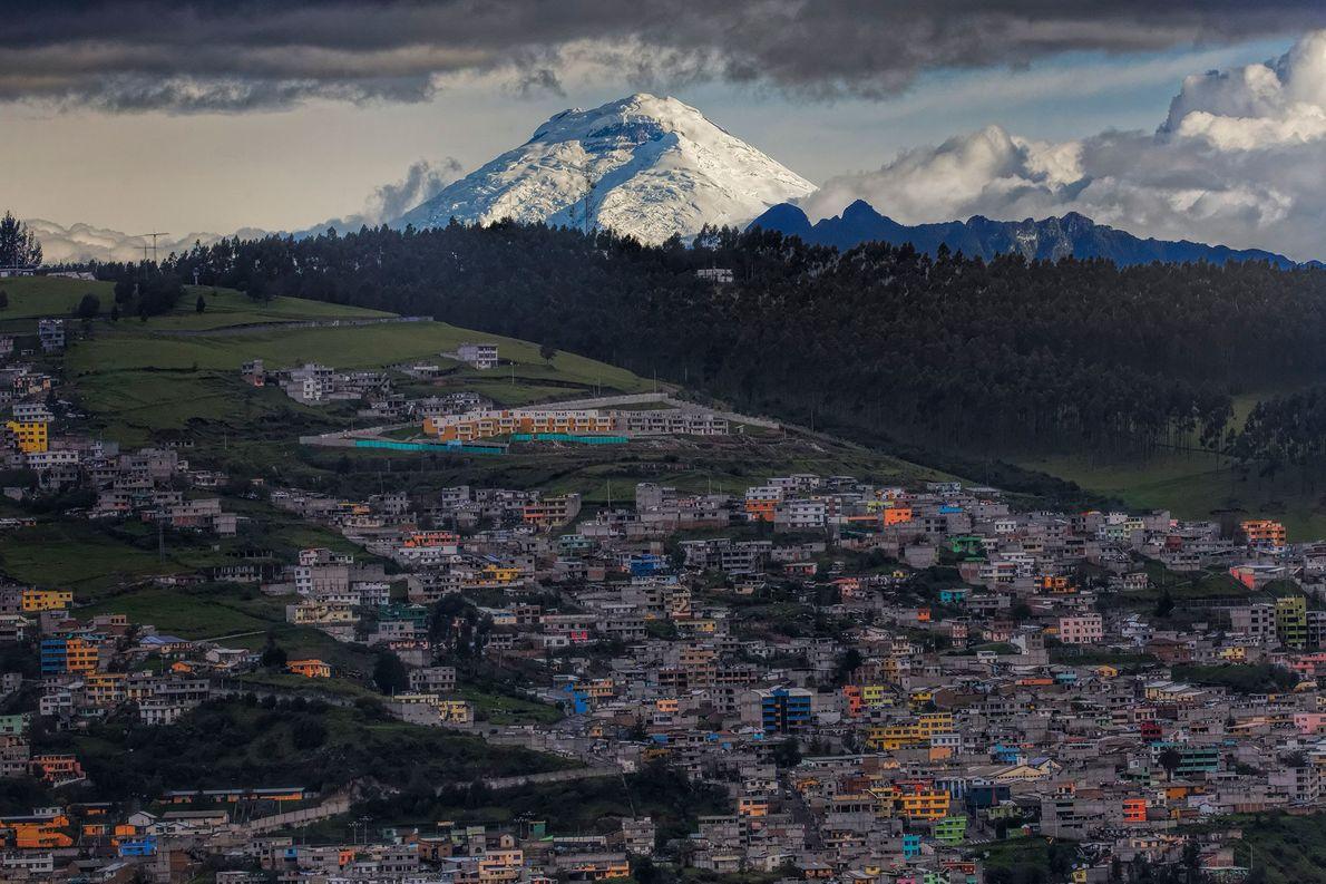 Lá do alto e coberta de neve, Cotopaxi observa Quito, onde as celebrações do Ano Novo ...