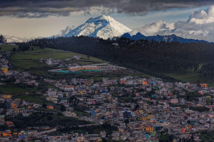 Lá do alto e coberta de neve, Cotopaxi observa Quito, onde as celebrações do Ano Novo …