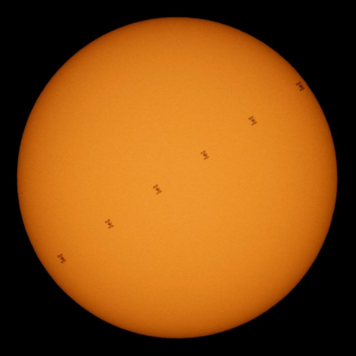 Uma marcha de pontos negros contra um disco brilhante: a Estação Espacial Internacional transita o sol ...