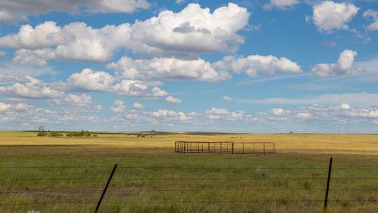 Nuvens brancas flutuam sobre um campo vazio no Monumento Nacional de Upper River Breaks em Montana. ...