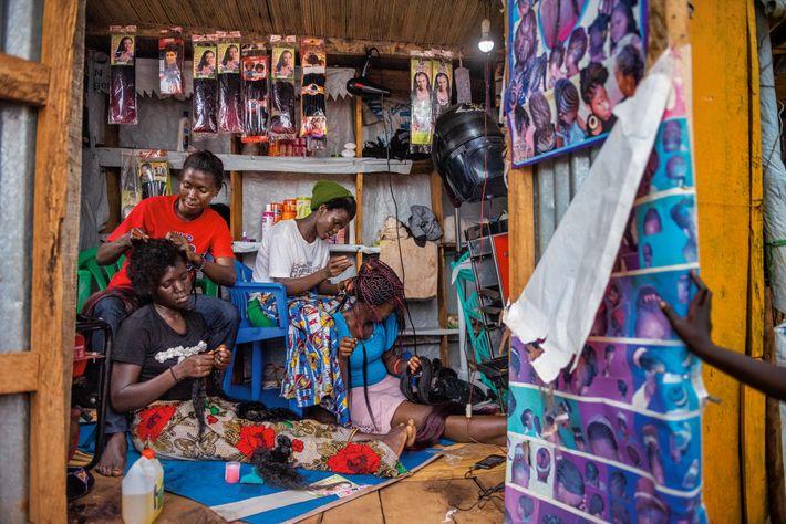 Knight Mai (à esquerda) e Florence Stima (à direita), sul-sudanesas, trabalham num salão em Bidibidi, um ...