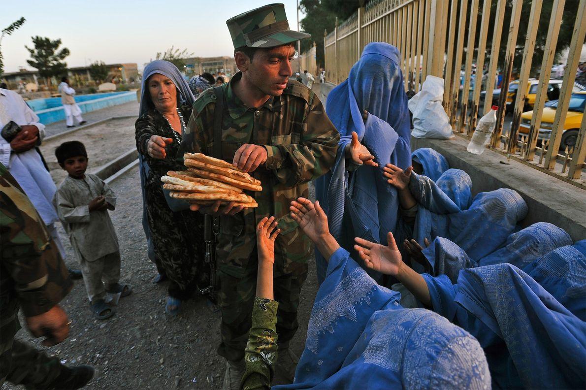 Soldado do Exército Nacional Afegão distribui pão