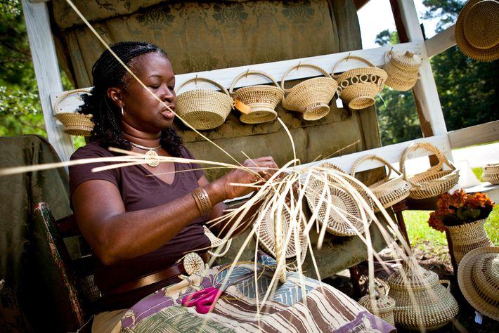 Barbara Manigault, tecelã de cestas de verga, pratica o seu ofício em Mount Pleasant, na Carolina ...