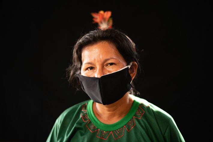 Uma mulher do grupo étnico Karapanã usa uma máscara facial costurada à mão, na esperança de ...