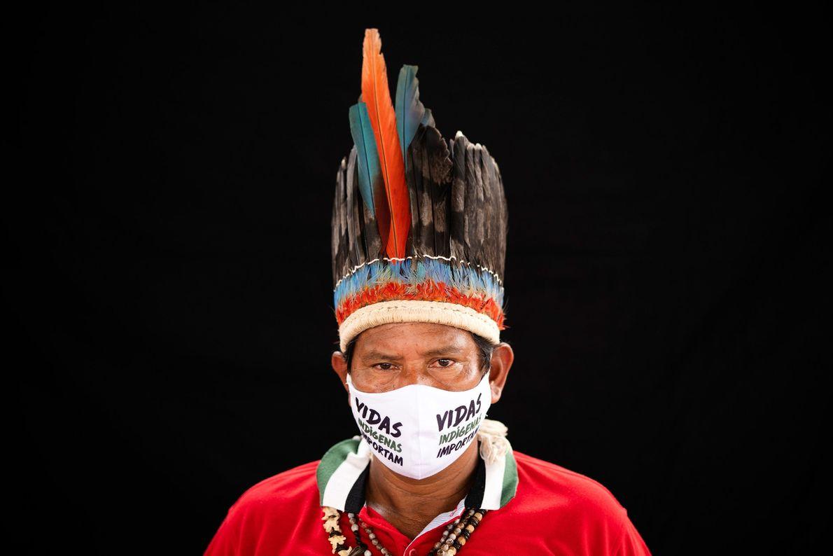 Um líder da tribo Miranha usa um cocar tradicional e uma máscara facial que diz Vidas ...