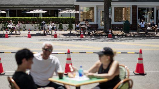 Clientes sentados em esplanadas de restaurantes que foram instaladas ao ar livre em ambos os lados ...